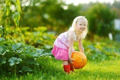 拿着南瓜的逗人喜爱的小女孩 图库摄影