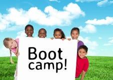 拿着卡片的孩子显示文本在蓝天和草前面的新兵训练所 免版税图库摄影
