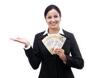 拿着印地安货币笔记的年轻女商人 库存照片