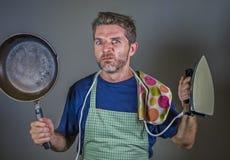 拿着厨房平底锅和铁在重音和被挫败的面孔表示的年轻可爱的被注重的和被淹没的懒惰人 免版税库存照片