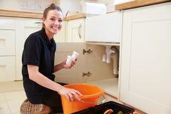 拿着厨房水槽的女性水管工一个U形管管子 免版税库存照片
