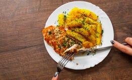 拿着叉子和刀子有烤鸡胸脯的妇女手用土豆在一块板材在木背景 免版税图库摄影