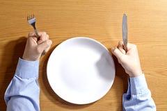 拿着叉子和刀子的男孩坐在与白色空的板材的桌上 免版税库存照片
