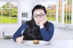 拿着叉子用土豆的肥胖妇女 免版税库存照片