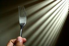 拿着叉子的手 免版税库存照片