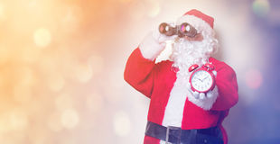 拿着双筒望远镜和闹钟的圣诞老人 库存照片