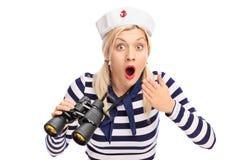 拿着双筒望远镜的惊奇的女性水手 库存照片