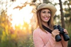 拿着双筒望远镜的美丽的少妇远足者在森林里 库存图片