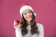 拿着发光的中看不中用的物品的圣诞节帽子的俏丽的夫人 库存照片