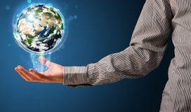 拿着发光的地球地球的商人 免版税库存图片