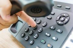 拿着受话器的男性手特写镜头,当拨电话号码打电话时 免版税库存图片