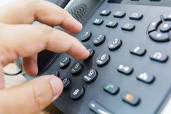 拿着受话器的男性手特写镜头,当拨电话号码打电话时 库存照片