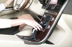拿着变速杆的妇女手 免版税库存图片