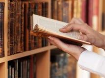 拿着古老书的妇女手 免版税库存图片