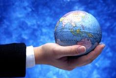 拿着古色古香的地球(亚洲地区)的手 免版税库存照片