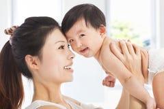 拿着可爱的儿童男婴的愉快的母亲 免版税库存图片