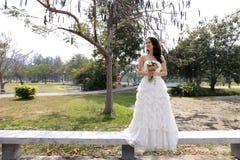 拿着可爱的花束的白色新娘婚装的亚裔新娘在庭院里 库存图片