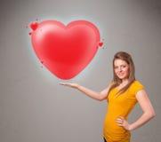 拿着可爱的3d红色心脏的小姐 免版税库存图片
