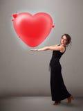 拿着可爱的3d红色心脏的小姐 库存图片