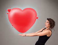 拿着可爱的3d红色心脏的小姐 免版税图库摄影