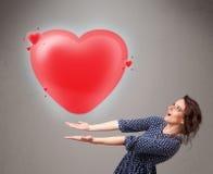 拿着可爱的3d红色心脏的小姐 图库摄影