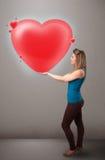 拿着可爱的3d红色心脏的小姐 免版税库存照片