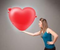 拿着可爱的3d红色心脏的小姐 库存照片