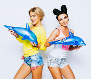 拿着可膨胀的玩具海豚的两个快乐的女朋友 穿戴在夏天明亮的成套装备,牛仔布短缺 获得乐趣和 免版税库存图片