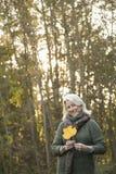 拿着叶子的资深妇女 免版税库存图片