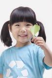 拿着叶子,演播室射击的关闭的小女孩 免版税库存照片