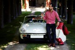 拿着司机或高尔夫俱乐部的英俊的高尔夫球运动员,当准备好在路线时的一天 库存图片
