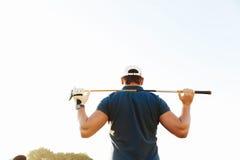 拿着司机的男性高尔夫球运动员,当站立在绿色路线时 免版税库存图片