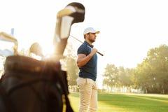 拿着司机的男性高尔夫球运动员,当站立时 库存图片