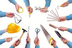 拿着各种各样的手工业贸易工具的男性工作者的手 免版税库存图片