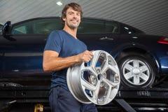 拿着合金的微笑的技术员在维修车间 免版税库存照片