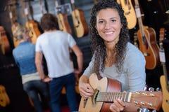 拿着吉他的妇女在吉他商店 库存照片
