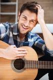 拿着吉他的愉快的英俊的年轻人 库存图片
