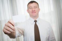 拿着名片的领带的愉快的人 免版税库存照片