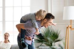 拿着后面的愉快的爸爸孩子儿子背上给乘驾 免版税图库摄影