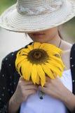 拿着向日葵的一个美丽的女孩 库存图片
