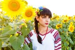 拿着向日葵的embrodery的美丽的妇女 免版税库存图片