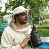 拿着吸烟者的防护服装的蜂农 图库摄影