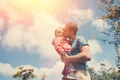 拿着和亲吻他逗人喜爱的女儿的年轻父亲,当花费时间户外时 图库摄影