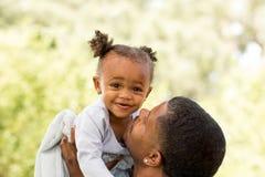 拿着和亲吻他的女儿的父亲 免版税库存照片