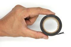 拿着和使用一卷绝缘胶带的人手隔绝在白色背景 免版税库存照片