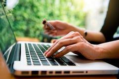 拿着和使用膝上型计算机的妇女购物的网上手 免版税图库摄影