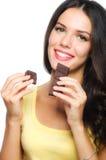 拿着和吃巧克力的Beuaitiful微笑的女孩被隔绝  库存图片