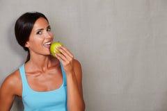 拿着和吃苹果的微笑的妇女 免版税库存照片