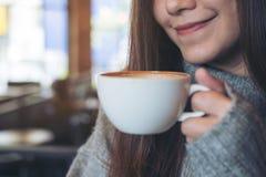 拿着和喝在冬时的一名亚裔妇女热的咖啡 图库摄影