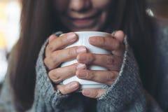 拿着和喝在冬时的亚裔妇女热的咖啡 免版税库存图片